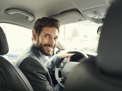 beared man in drivers seat of car