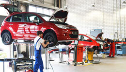red hatchback on hoist in service department